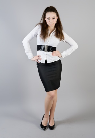 girl in a white blouse and a black skirt on a gray background photo