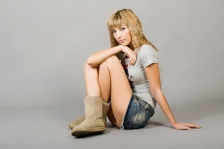 La jeune fille dans une blouse grise et une jupe de jeans