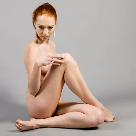Portrait of the young nude woman on a gray background Stock Photo