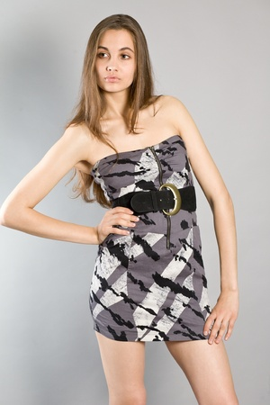 Portrait of the young long-haired girl in an elegant dress on a gray background photo