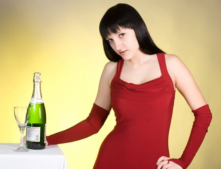The girl in a red dress with a champagne glass photo
