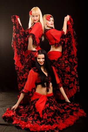 Three beautiful girls in Gipsy suits on a black background photo