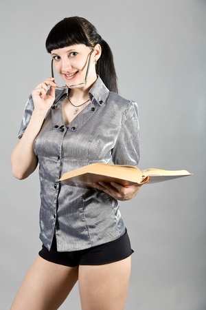 girl wearing spectacles and with the book in hands photo