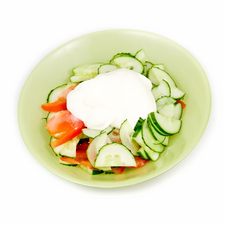 Salad from tomatoes and cucumbers with sour cream photo