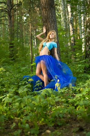 The blond long-haired girl in summer wood photo