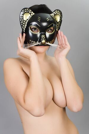 The naked girl in a mask of a cat  Isolated on grey
