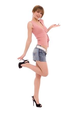 La grande fille aux longues jambes dans une jupe de jeans isolé sur blanc