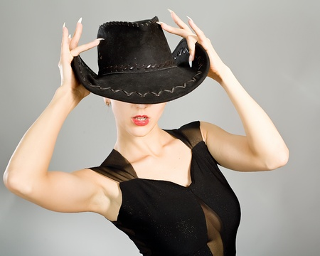 Portrait of the young girl in an elegant black dress and a hat photo