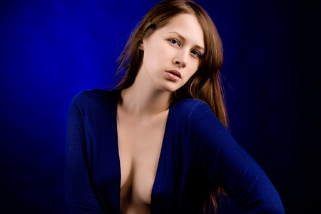 Portrait of the young woman on a dark blue background