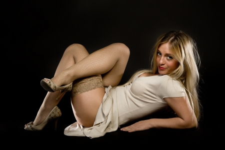young woman in stockings with legs crossed on a black background Stock Photo - 13699237