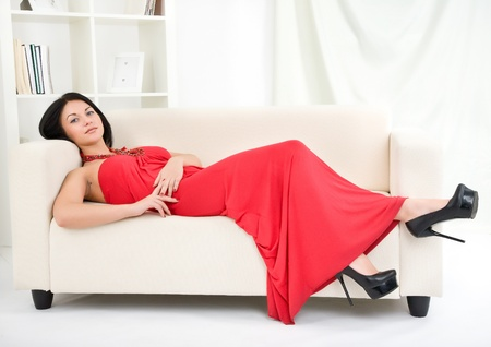attractive brunette in a red dress on a sofa photo