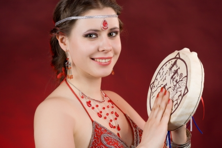 portrait of a beautiful girl with a shaman tambourine photo