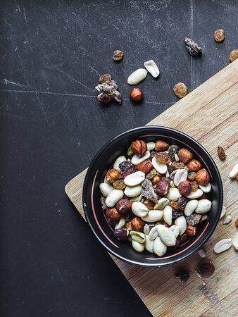 Top view of black bowl with nuts and dried fruits on the wooden cutting board with black chalkboard background. Several types of nuts including hazel-nuts and peanuts. Фото со стока