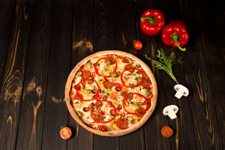 Side view of pizza with bell pepper, green olives, smoked sausages, mozzarella cheese, pepperoni, salami, chili pepper, champignons on wooden background. Tasty uncut pizza with ingredients and herbs
