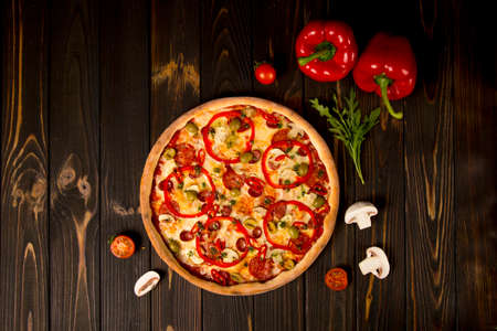 Top view of pizza with bell pepper, green olives, smoked sausages, mozzarella cheese, pepperoni, salami, chili pepper, champignons on wooden background. Tasty uncut pizza with ingredients and herbs