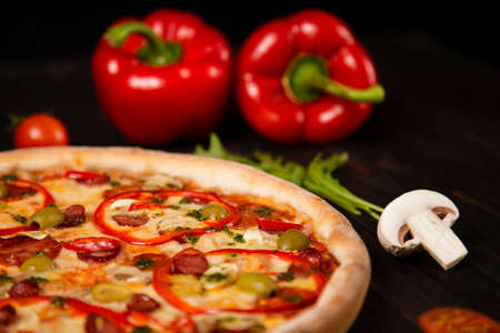 Side view of pizza with bell pepper, green olives, smoked sausages, mozzarella cheese, pepperoni, salami, chili pepper, champignons on wooden board with ingredients on background. uncut tasty pizza