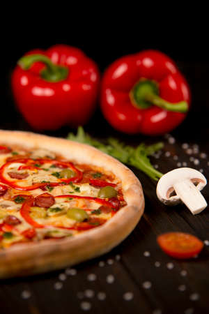 Half of pizza with bell pepper, green olives, sausages, mozzarella cheese, pepperoni, salami, chili pepper, champignons on wooden board with two bell peppers on background. Close up of uncut pizza Reklamní fotografie