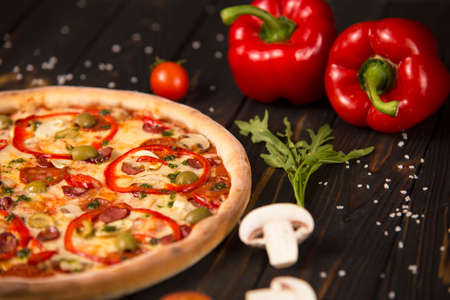 Part of pizza with bell pepper, champignons, cherry tomatoes and herbs on wooden board background. Close up of uncut pizza