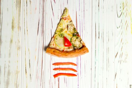 Top view of traditional Italian pizza with zucchini, bell pepper, eggplant, cheese, tomato sauce and pesto sauce on light wooden background. Pieces of ingredients near Tasty Slice of vegetable pizza