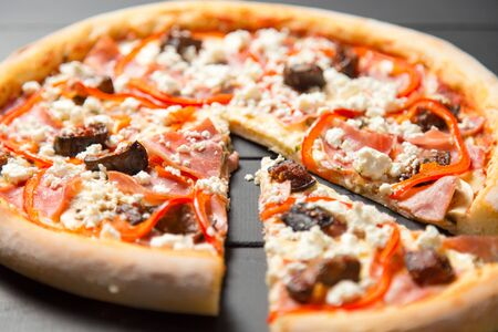 Close up of traditional Italian pizza with ham, beef, bell pepper, mozzarella cheese and tomato sauce on dark wooden background. Slice of pizza moved near the whole dish. Delicious Mediterranean meal
