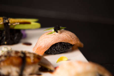Set of Japanese nigiri. Close up of Salmon Sake Tataki with black rice, mayonnaise, flying fish roe (Tobiko caviar) in focus. Decorated food plate on dark wooden background. Asian restaurant menu Reklamní fotografie