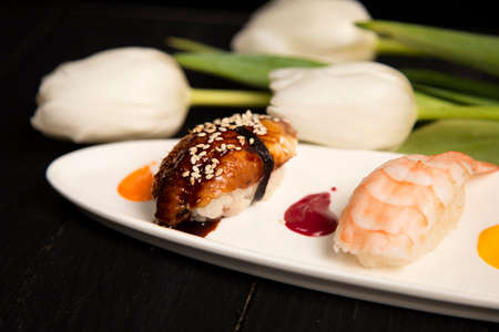 Japanese Nigiri Unagi Sushi with eel in focus near nigiri Ebi with tiger shrimp. colourful food decoration painting spots on plate near white tulips. Pan Asian restaurant menu on dark wooden board Reklamní fotografie