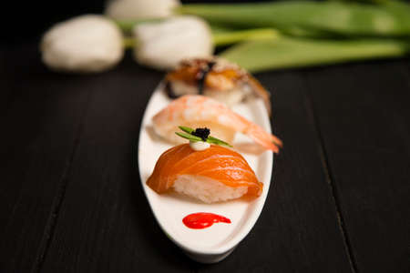 Set of Japanese Nigiri Sushi with salmon in focus near nigiri Ebi with shrimp and Unagi with eel. white plate with colourful food decoration painting spots. Asian restaurant seafood menu. Close up
