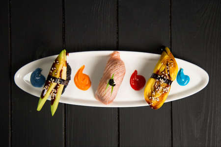 Set of Japanese Nigiri Sake Sushi with salmon Tataki near nigiri with avocado and Tamagoyaki with omelette. food decoration paints on white plate. Pan Asian restaurant menu top view on wooden board