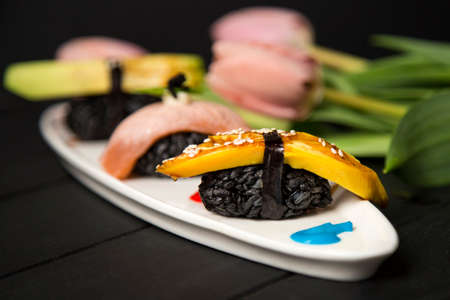 Set of Japanese nigiri. Close up of Nigiri Tamagoyaki with black rice, omelette and sesames in focus, pink tulips. Raw food plate decorated with paints on dark wooden board. Pan Asian seafood menu