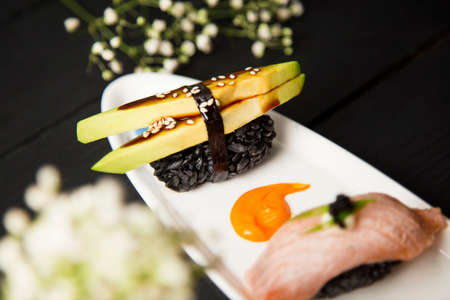 Japanese Nigiri Sushi with avocado, sesame seeds and Unagi sauce in focus on white plate decorated with colour paints. food decoration. Pan Asian seafood restaurant menu cuisine concept with flowers Reklamní fotografie