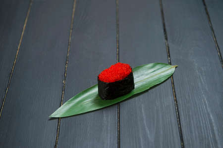 Close up of Japanese Tobiko Gunkan Sushi on bamboo leaf, dark wooden board. Traditional Pan Asian restaurant menu cuisine concept. Nori wrapped red flying fish roe sushi. Raw eastern food