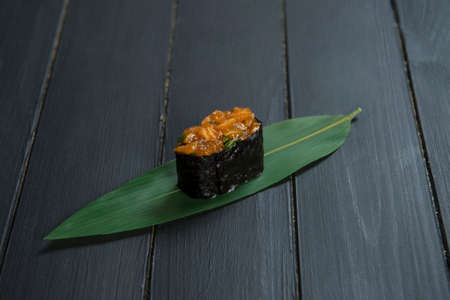 Close up of Japanese Gunkan Sake Maki Sushi roll with marinated salmon and greens on bamboo leaf on black wooden board. Reklamní fotografie