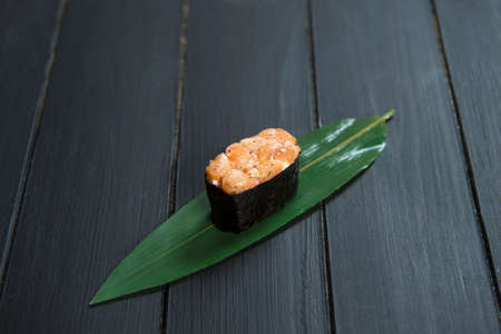 Close up of Japanese Gunkan Maki Sushi with salmon on bamboo leaf on black wooden board. Background image cuisine concept. Traditional Sake maki sushi roll. Pan Asian delicatessen restaurant food menu
