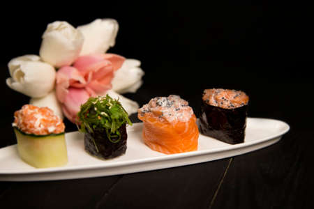 Set of Japanese Gunkans. salmon Sake with Tobiko caviar in focus on white plate. Asian dish on wooden board with pastel tulip flowers on background. Expensive raw seafood Asian restaurant menu Reklamní fotografie