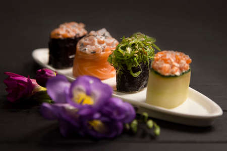 Set of Japanese Gunkans with Hiyashi wakame chuka maki roll in focus on white plate near. Asian traditional dish with salmon on dark wooden board with flowers. Delicatessen Sushi restaurant menu