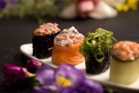 Set of Japanese Gunkans. salmon Sake with Tobiko caviar in focus on white plate. Asian dish on wooden board with colourful flowers on background. Expensive raw seafood Asian restaurant menu