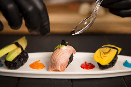 Serving black Tobiko caviar on Japanese Nigiri Sushi Sake with salmon Tataki on white plate. Chef hands in protection gloves using tea spoon. Pan Asian Restaurant Food decoration process.