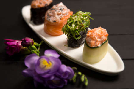 Set of Japanese Gunkans with Hiyashi wakame chuka maki roll in focus on white plate near. Asian dish with salmon on dark wooden board with flowers. Sushi restaurant menu close up. Expensive food