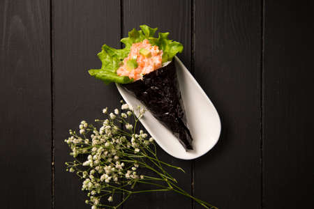 Japanese Sushi Sake Temaki with salmon, rice, Tobiko roe eggs, avocado and salad leaf in nori seaweed on plate. White flowers on background. Close up of Pan Asian traditional dish. Top view