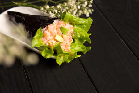 Japanese Sushi Sake Temaki with salmon, rice, Tobiko roe eggs, avocado and salad leaf in nori seaweed on plate. White flowers on background. Close up of Pan Asian traditional dish. Restaurant menu Reklamní fotografie