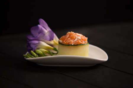 Japanese Gunkan Sake Green sushi with salmon and cream cheese in cucumber on white plate. Violet flower near Asian traditional dish on dark wooden background. Sushi restaurant menu. Seafood raw sushi