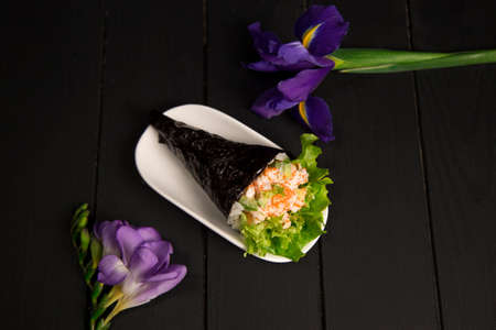 Japanese Sushi Temaki with tiger shrimp, rice, Tobiko caviar and salad leaf in nori seaweed on white plate. Iris flower on dark wooden board. Close up of Pan Asian traditional dish. top view