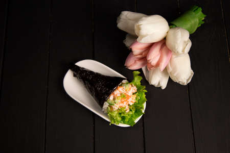 Japanese Sushi Temaki with tiger shrimp, rice, Tobiko roe eggs and salad leaf in nori seaweed on white plate. Tulips on dark wooden board. Close up of Pan Asian traditional dish. Restaurant menu