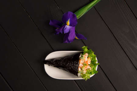 Japanese Sushi Temaki with tiger shrimp, rice, Tobiko roe eggs and salad leaf in nori seaweed on white plate. Iris flower on dark wooden board. Close up of Pan Asian traditional dish. Restaurant menu