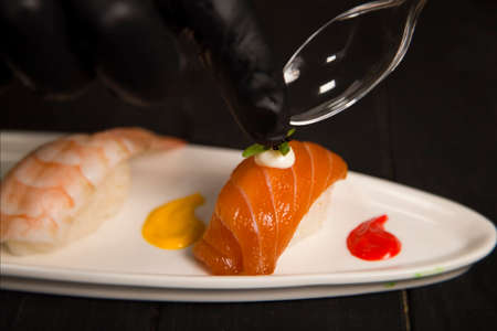Serving flying fish roe (Tobiko) on Japanese Nigiri Sushi with salmon. Chef hands in protection gloves using tea spoon. Pan Asian Restaurant Food decoration process. Nigiri Sake near Ebi with shrimp