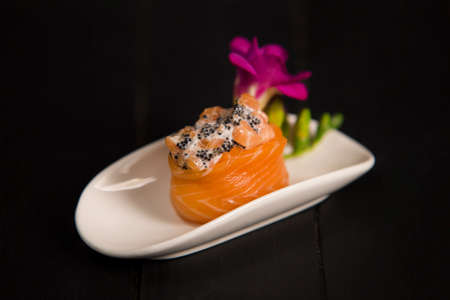 Japanese Gunkan sushi with fresh salmon and Tobico caviar on white plate decorated with flower. Asian traditional dish on dark wooden background. Pan Asian restaurant menu. Seafood maki sushi roll