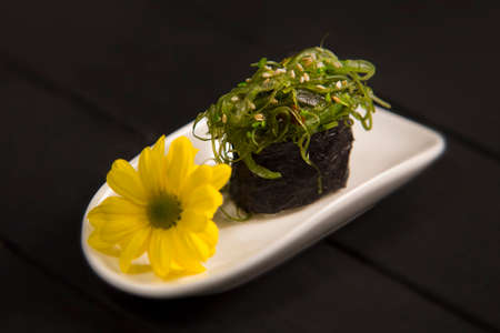 Japanese Chuka seaweed gunkan sushi with Hiyashi wakame and sesames on white plate, Yellow camomile flower. Asian traditional meal on wooden board. Sushi restaurant menu close up. Raw vegetarian food Reklamní fotografie