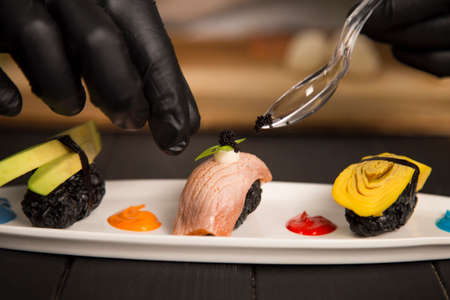 Serving black Tobiko caviar on Japanese Nigiri Sushi Sake with salmon Tataki on white plate. Chef hands in protection gloves using tea spoon. Asian Restaurant Food decoration process. Cuisine concept