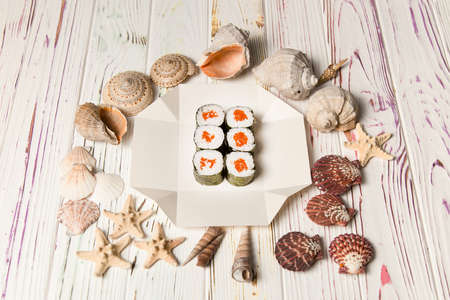 Side view of Japanese Sake Maki Roll with salmon and rice wrapped in nori seaweed on white carton delivery box. Sea shells and stars on wooden background. Food delivery creatice concept menu