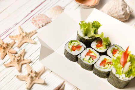 Japanese Futomaki Sushi Roll pieces on carton delivery box. Asian Vegetable Maki roll with tomato, cucumber, avocado, paprika, salad mix on wooden board with sea shells and stars on background